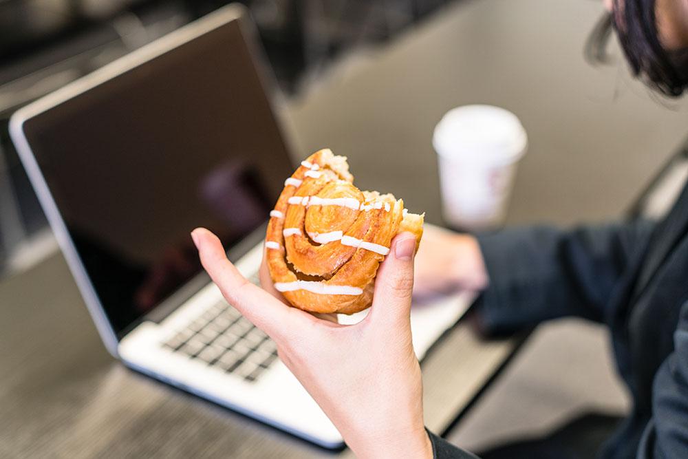 Woman eating sugary cinnamon roll